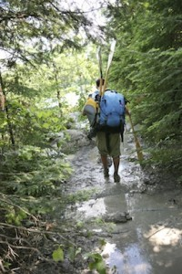 Picture of man carrying pack, PFD and paddles