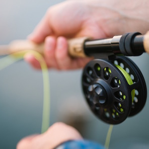 Close-up picture of a fly cast rod and reel being held by a person learning to cast