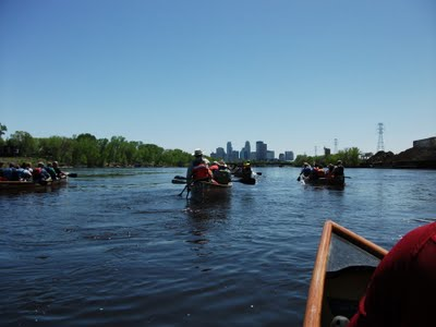 Picture of canoeists paddling toward a city