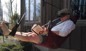 Picture of CJ relaxing in the ENO Lounger while she reads a book