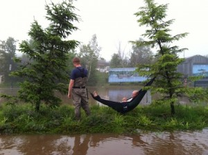 Picture of Jacob relaxing in an Eno Hamock while Scott looks on. They are on an island of grass in the otherwise flooded Stone Harbor parking lot.