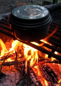 Picture of a cast iron pot and cover sitting on a grate over an open fire