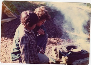 Picture of a young boy and his father cooking by a camp fire