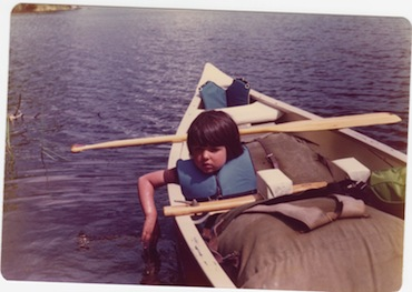 Picture of a young boy sitting in a canoe