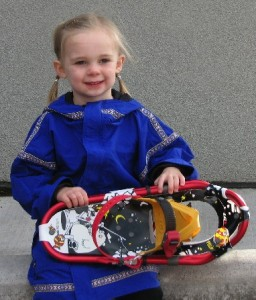 Picture of a little girl wearing a blue Wintergreen Anorak and holding snow shoes