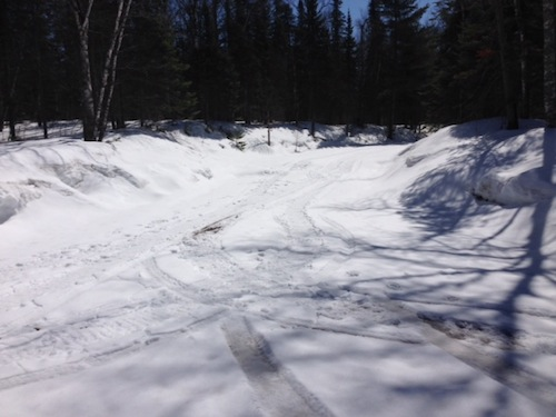 Picture of the Forest Service Road going into Kimball Lake Campground. The road is entirely covered with snow and you can barely see some tire tracks on the snow.