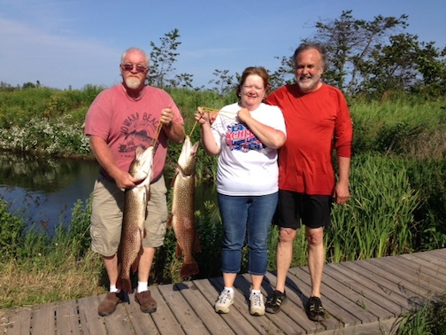 Picture of Jeff and Cathy Olson, and Jack Stone. Jeff and Cathy are each holding a very large Northern fish that they caught.