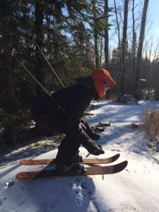 Picture of Jan on Hok skis looking down a small slope for more snow.