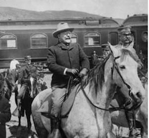 Picture of Theodore Roosevelt seated on a horse. In the background there is a train car and several other men on horseback.
