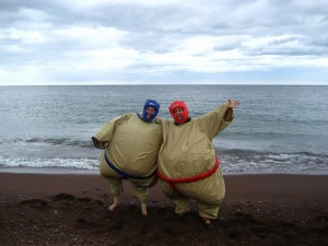 Picture of two women in inflatable sumo wrestler suits with Lake Superior in the background.