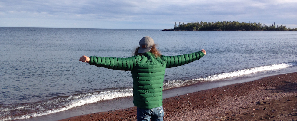 Picture of Josh's back as he's wearing the Mountain Hardware jacket while he is looking at Lake Superior and stretching his arms out