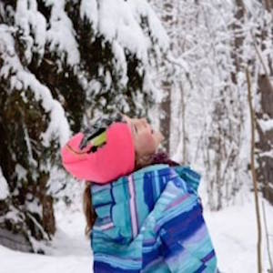 Picture of a young girl pausing from her snowshoe trek to catch snowflakes in her mouth