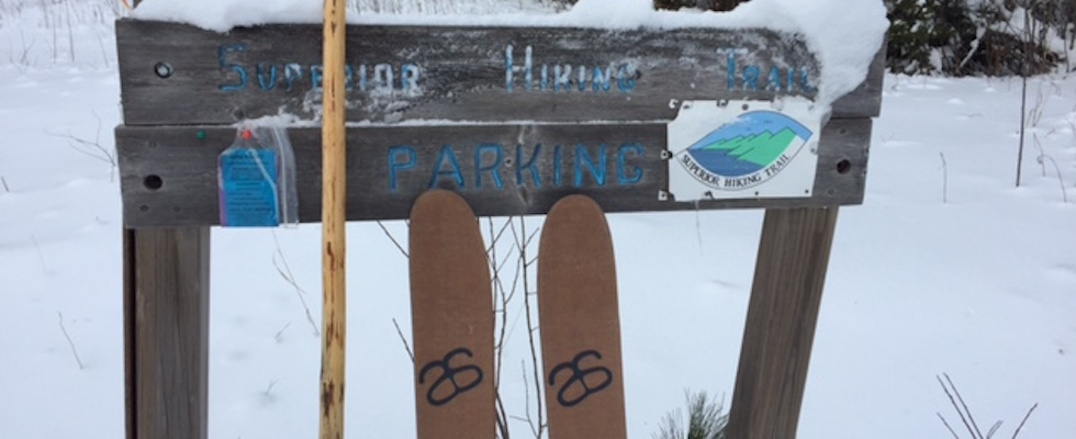 Picture of HOK skis resting against a sign for the Superior Hiking Trail