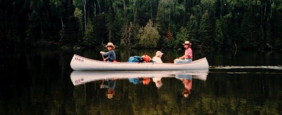 Picture of three people in a canoe. The person in the middle is fishing