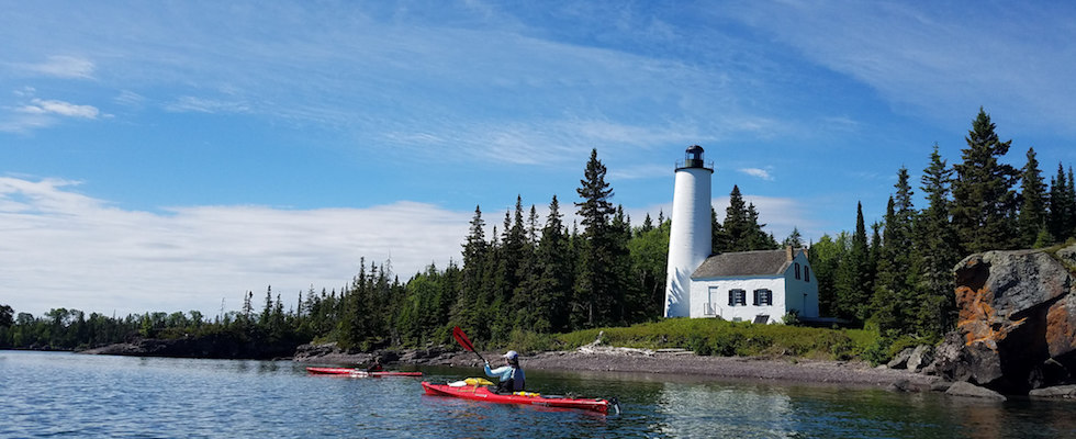 Picture of kayakers paddling by Light House on Isle Royale