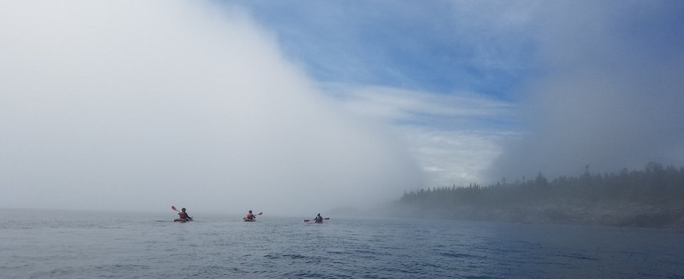 Picture of sea kayakers paddling through the mist at Isle Royale