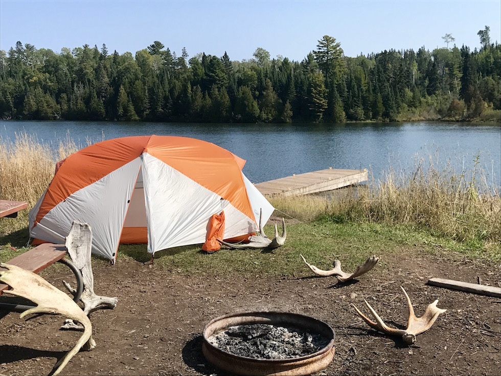 Picture of tent on the lakeshore, surrounded by moose antlers, on Isle Royale