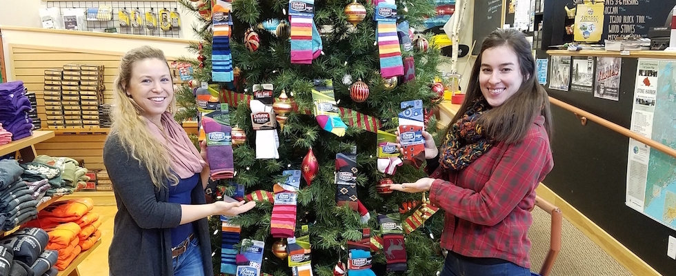 Picture of Claire and Natalie standing by a Christmas tree decorated with socks