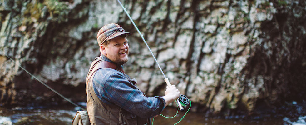 Picture of a man fly-fishing with a stream and rock face in the background