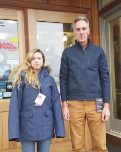 Another picture of a short woman in a long jacket and a tall man in a short jacket