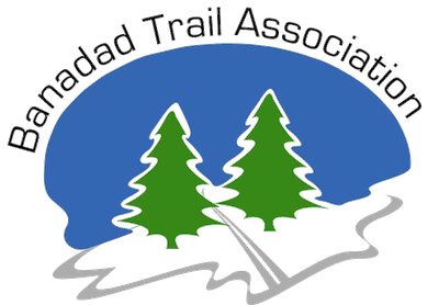 Banadad Trail Association logo depicting two pine tress in background and a cross-country ski trail in the foreground