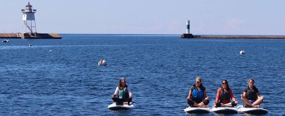 Picture of four women doing paddle board yoga in the Grand Marais harbor