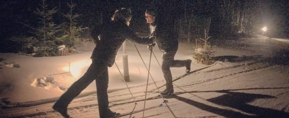 Picture of two people cross-country skiing on a lighted night trail