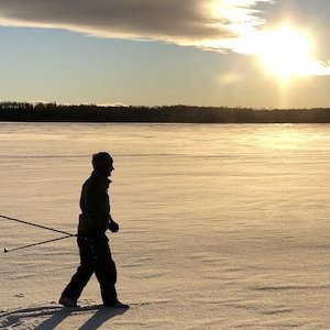 Silhouette of a cross-country skier as the sun begins to set on a winter day