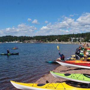 Picture of people looking t and trying various kayaks at a recent North Shore Water Festival in Grand Marais, MN
