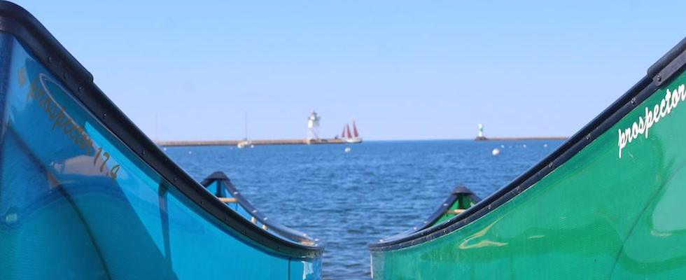 Picture of two Nova Craft Prospector canoes in the foreground, with the Grand Marais Harbor (including the Light House and the Schooner Hjordis) in the background