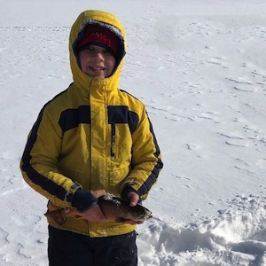Picture of a boy holding a fish he just caught while ice fishing