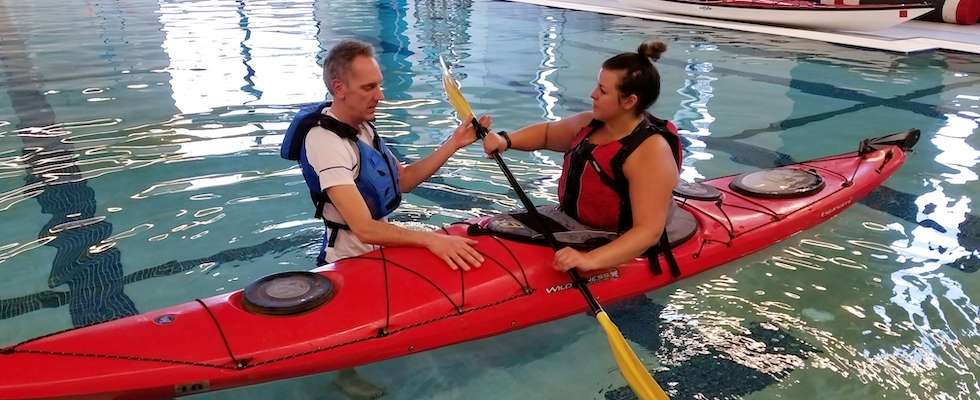 Picture of Kris teaching Jen a kayak safety maneuver in the YMCA pool