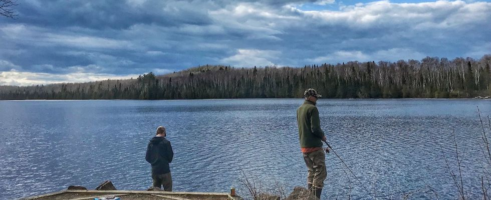 Picture of two men fishing on the shore of a lake in Grand Marais, MN