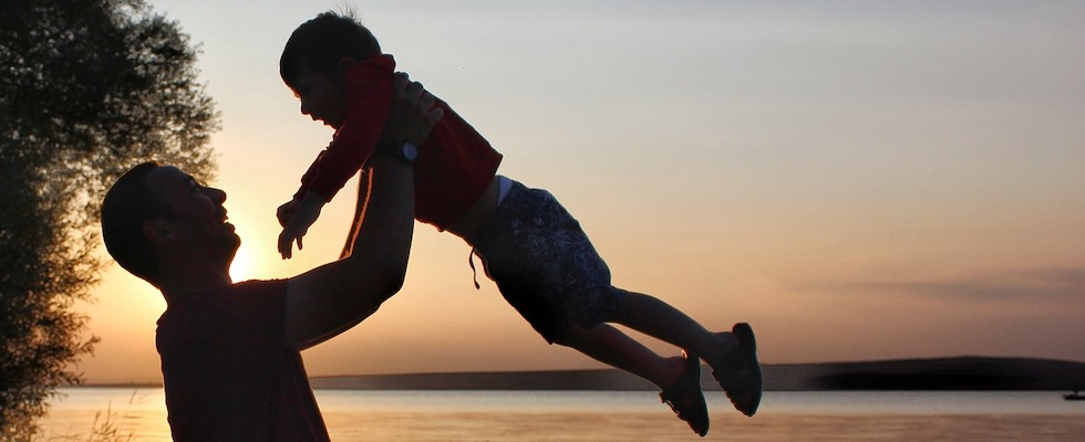 Silhouette of a father lifting his child in the air at sunset with the lake in the background