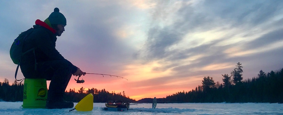 Picture of Mike ice fishing with the sunset in the background