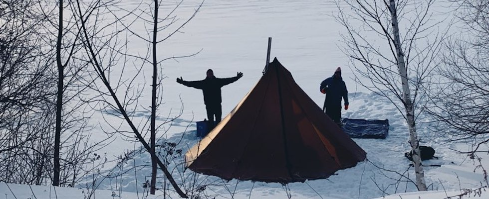 Picture of two happy winter campers outside of their tent