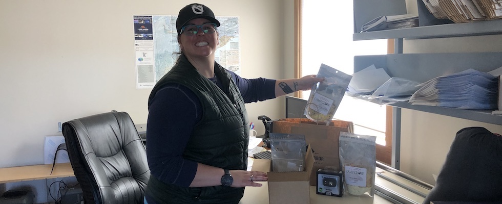 Picture of Jen packing a box of Camp Chow and gear for one of our customers