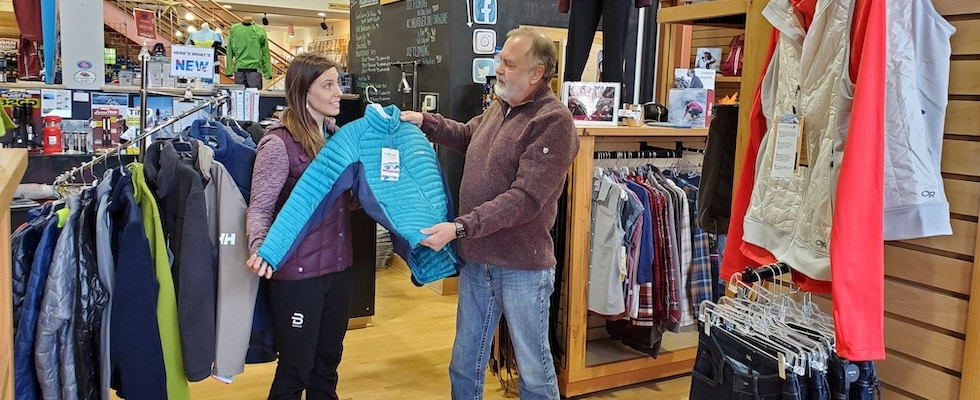 A picture of Beth and Jack selecting clothing items for a customer