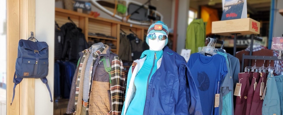 Picture of the Stone Harbor Wilderness Supply front window showing spring clothes