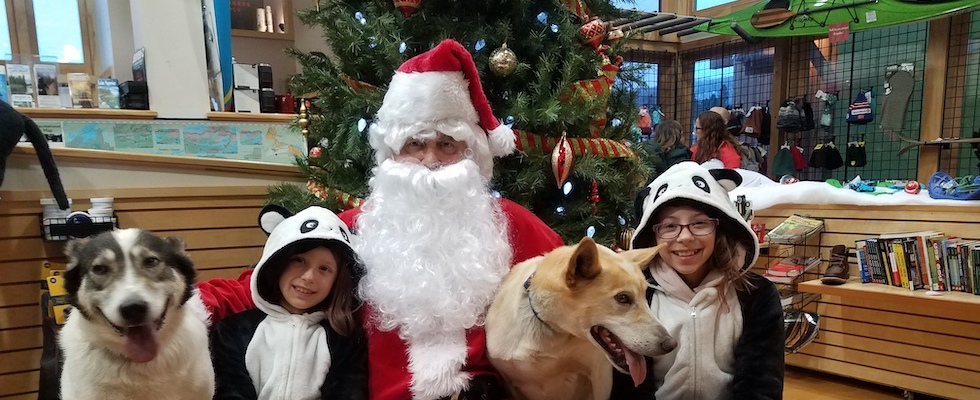 Picture of Santa and his sled dogs, along with two girls